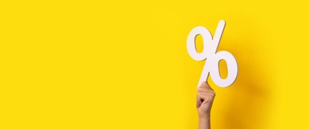Sinal de porcentagem em mãos sobre fundo amarelo, maquete panorâmica