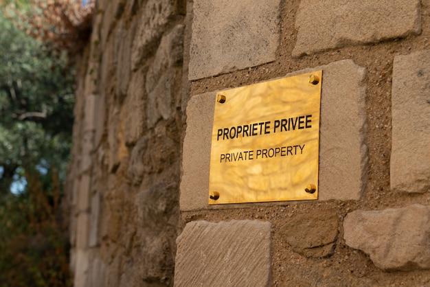 Sinal de propriedade privada dourada em francês e inglês ouro ou latão na parede
