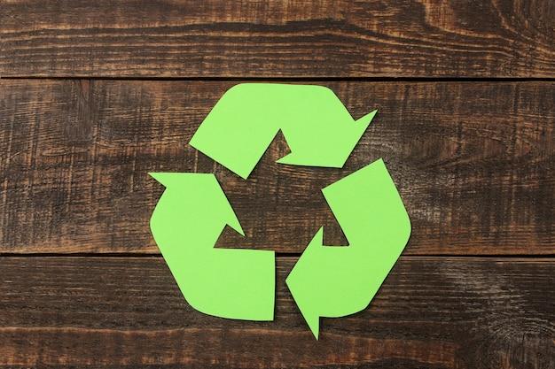 Sinal de reciclagem em uma mesa de madeira marrom. vista de cima. conceito ecológico