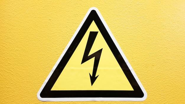 Sinal de segurança amarelo e preto colado na parede amarela. relâmpago de alta tensão em um triângulo cuidado, perigo, eletricidade, morte.