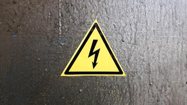 Sinal de segurança amarelo e preto em um fundo de metal prateado. relâmpago de alta tensão em um triângulo cuidado, perigo, eletricidade, morte.