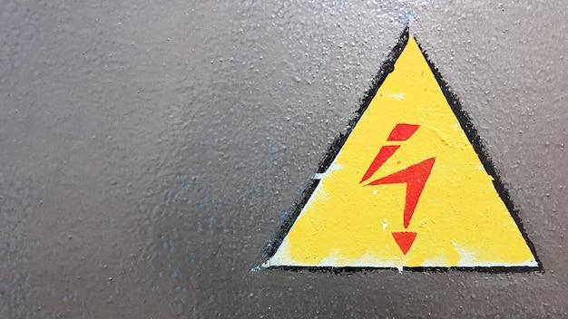 Sinal de segurança amarelo e vermelho em um fundo de metal prateado. relâmpago de alta tensão em um triângulo cuidado, perigo, eletricidade, morte.