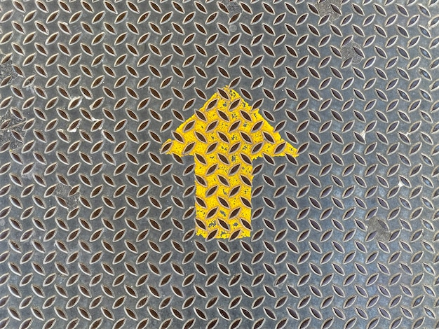 Sinal de seta amarelo para cima na placa de metal
