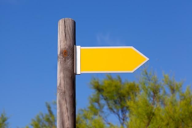 Sinal de seta copyspace amarelo no poste de madeira