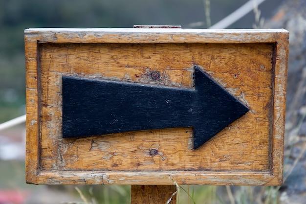 Sinal de seta no poste de madeira