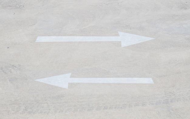 Sinal de seta pálida closeup no chão de cimento no parque de estacionamento