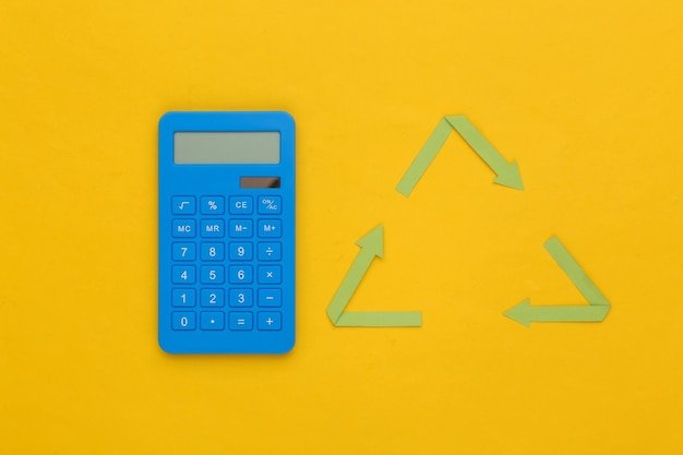 Sinal de setas recicladas e calculadora em fundo amarelo. vista do topo
