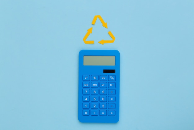 Sinal de setas recicladas e calculadora sobre fundo azul. vista do topo