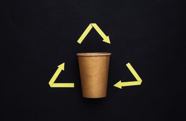 Sinal de setas recicladas e xícara de café em fundo preto. conceito ecológico. vista do topo