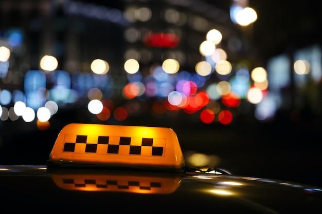 Sinal de táxi iluminado em uma rua da cidade