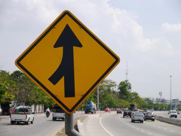 Sinal de tráfego rodoviário curvo na estrada ao lado do país