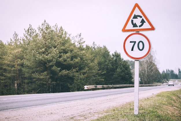 Sinal de trânsito com limite de velocidade de 70 e sinal de alerta de que em breve haverá uma estrada com tráfego circular, rotatória na bielorrússia