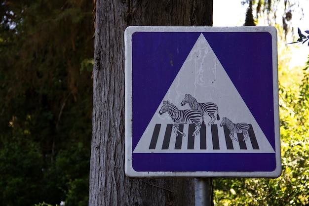 Sinal de trânsito com zebras cruzando faixas de pedestres.