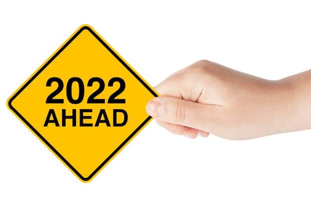 Sinal de trânsito de 2022 anos à frente na mão de uma mulher em um fundo branco