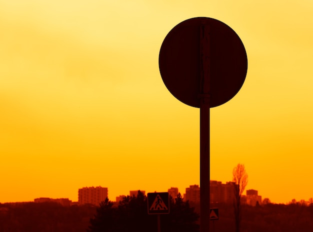 Sinal de trânsito do pôr do sol: vista traseira do plano de fundo