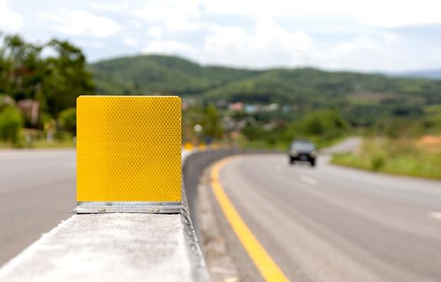 Sinal de trânsito reflexivo na barreira de concreto na estrada