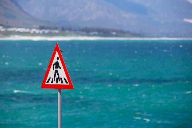 Sinal de travessia de pedestres e oceano azul ao fundo