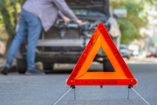 Sinal de triângulo de parada de emergência vermelha antes de carro destruído em acidente de trânsito na estrada da cidade. motorista de homem olhando para carro quebrado esmagado em acidente. copie o espaço.