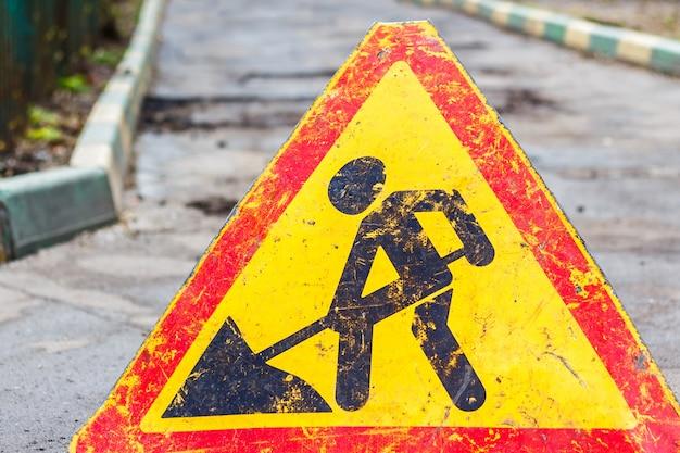 Sinal de um homem com uma pá. cuidado, obras rodoviárias estão em andamento