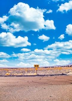 Sinal direcional no deserto com céu azul cênico e amplo horizonte. conceito de viagem, liberdade, férias e transporte.