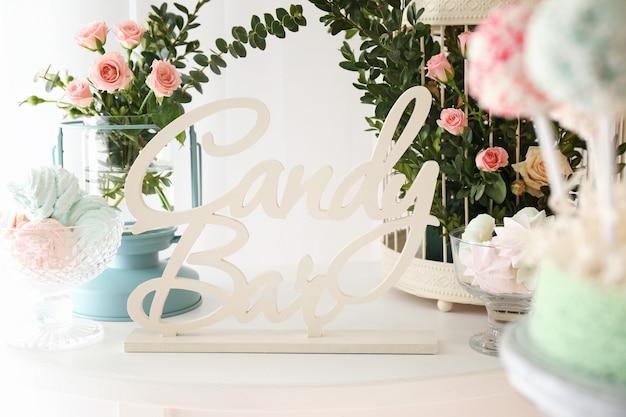 Sinal do candy bar e belas decorações de flores na mesa