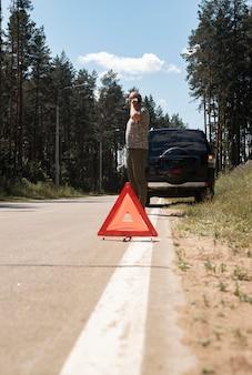 Sinal do triângulo vermelho na estrada lateral após a parada do carro e motorista falando no telefone celular chamando reparo automático ...