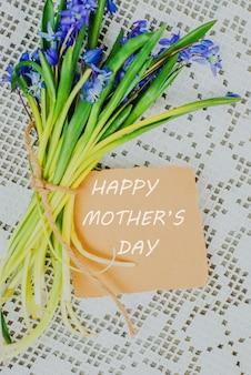 Sinal feliz do texto do dia de mães no cartão à moda do ofício e no siberica do scilla na toalha de mesa rústica branca.