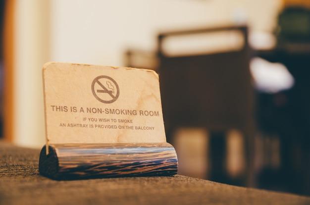 Sinal não fumadores de madeira no sofá na sala