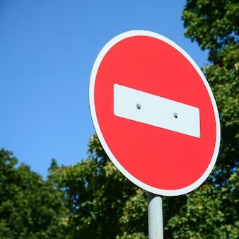 Sinal proibido vermelho com árvores no fundo