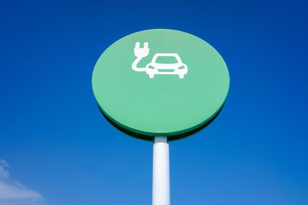 Sinal redondo de estação de recarga de carro elétrico, com fundo de céu azul e espaço de cópia.