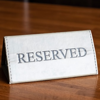 Sinal reservado em uma mesa de madeira em um restaurante. sinal de reserva de configuração de tabela