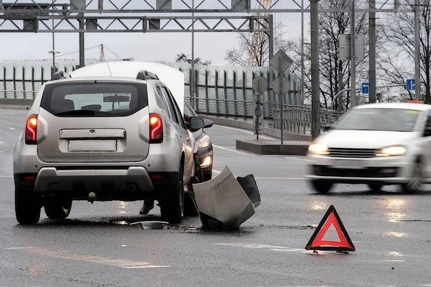 Sinal retro-reflexivo vermelho triangular de acidente na estrada. colisão de dois carros. pára-choque e capô quebrados. acidente de carro na rua.