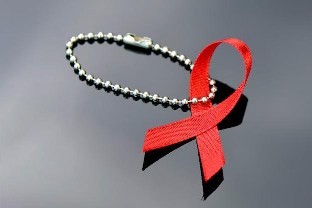Sinal vermelho da fita do dia mundial do sida no fundo escuro.