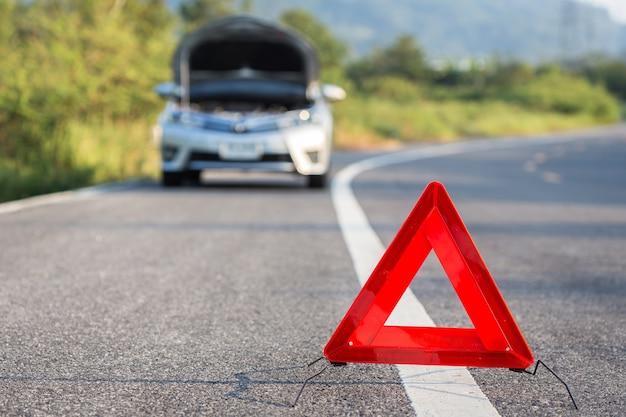 Sinal vermelho de parada de emergência e quebrado carro prateado na estrada