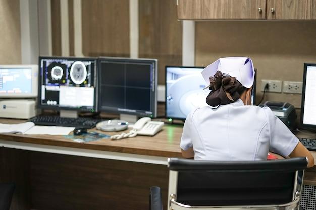 Sinal vital de registro de enfermeira na ficha médica na estação de trabalho de tomografia computadorizada roo
