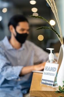 Sinalização de desinfetante para as mãos em torno do escritório para práticas de higiene após reabrir