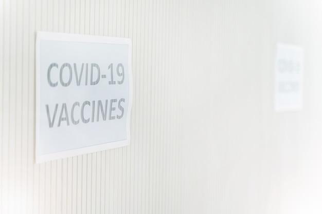 Sinalização na parede para obter a vacina covid na clínica ou hospital com fundo de parede branca.