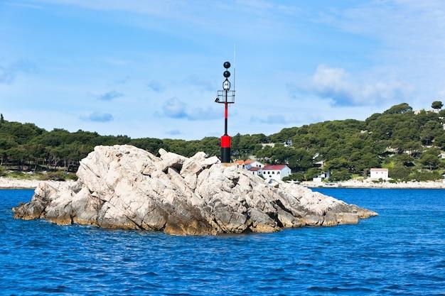 Sinalizador de perigo - sinal de perigo náutico em uma rocha no mar