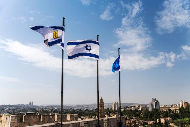 Sinalizadores de israel e jerusalém nas muralhas da cidade velha de jerusalém contra o céu azul com nuvens brancas na luz do sol. jerusalém, israel. 24 de outubro de 2018.