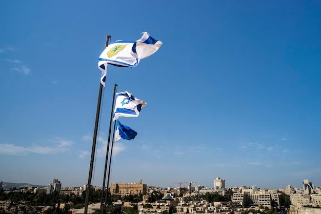 Sinalizadores de israel e jerusalém nas muralhas da cidade velha de jerusalém contra o céu azul com nuvens brancas na luz do verão ensolarado.