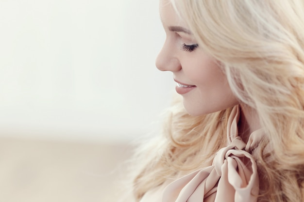 Sincera mulher loira bonita com cabelos ondulados, perfil ou vista lateral