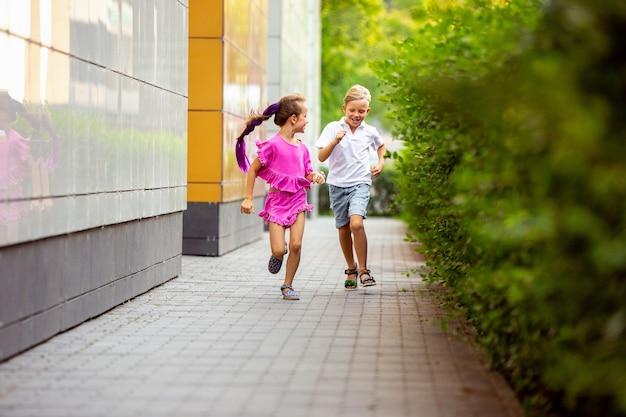 Sincero. duas crianças sorridentes, menino e menina correndo juntos na cidade, cidade em dia de verão. conceito de infância, felicidade, emoções sinceras, estilo de vida despreocupado. pequenos modelos caucasianos com roupas brilhantes.