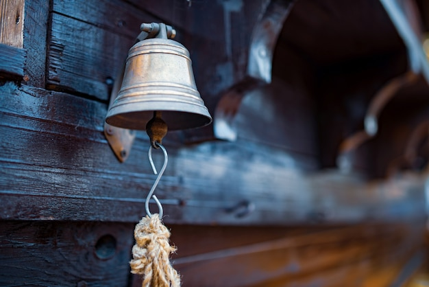 Sino com uma corda pendurado no casco de um navio de madeira. conceito de notificações ee situações de emergência no navio.