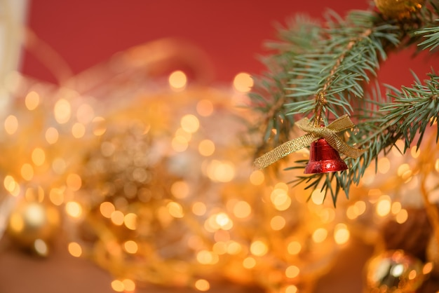 Sino de brinquedo de natal dourado em um galho de abeto no fundo de uma guirlanda de natal