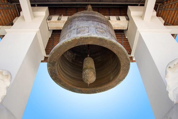 Sino de igreja velho com o céu azul no templo de lamphun, tailândia