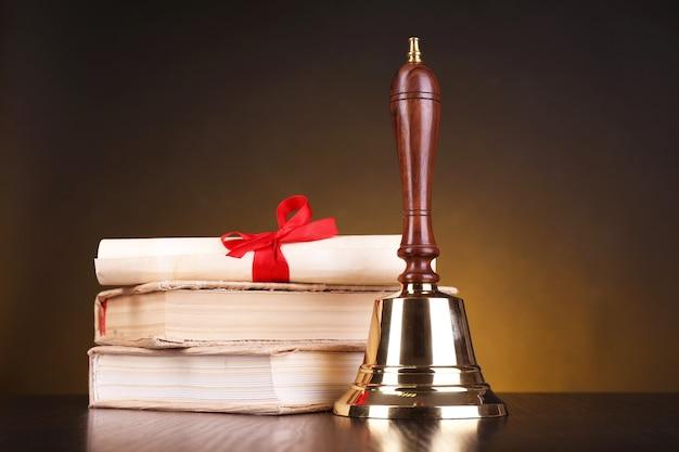 Sino escolar retrô dourado com livros na mesa em fundo escuro