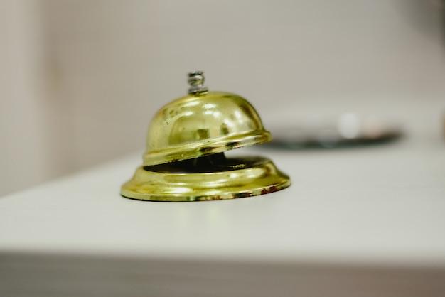 Sino velho para chamar o mensageiro em um hotel, serviço sino hotel dourado.