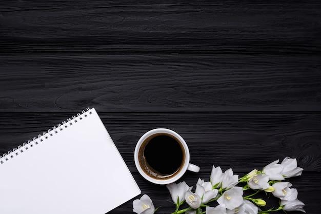 Sinos de flores brancas, café e caderno vazio para o seu texto em um fundo preto de madeira.