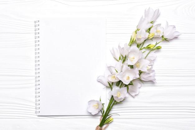 Sinos de flores brancas e caderno vazio para o seu texto em um fundo branco de madeira.