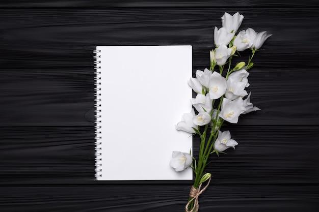 Sinos de flores brancas e caderno vazio para o seu texto em um fundo preto de madeira.
